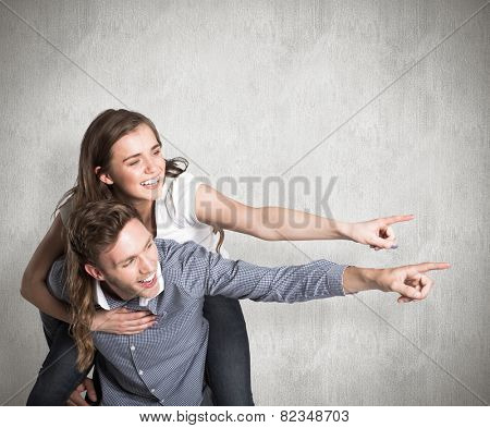 Smiling young man carrying woman against weathered surface