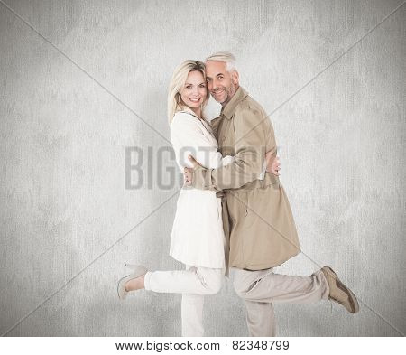 Happy couple posing in trench coats against white background