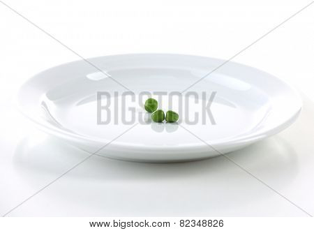 Remnants of peas on plate isolated on white