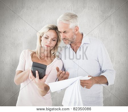 Anxious couple working out their bills against weathered surface
