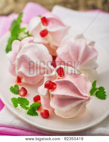 Meringue cookies in bowl with cream and pomegranate seeds