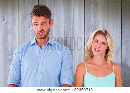 Young couple making silly faces against wooden planks