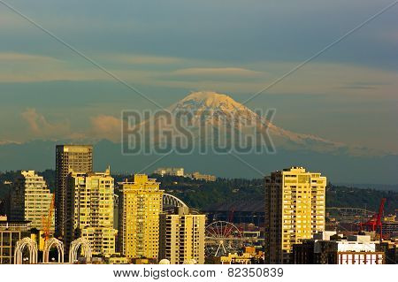 Mount Rainier and Seattle buildings at sunset hours.