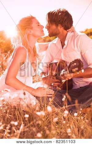 Handsome man serenading his girlfriend with guitar on a sunny day