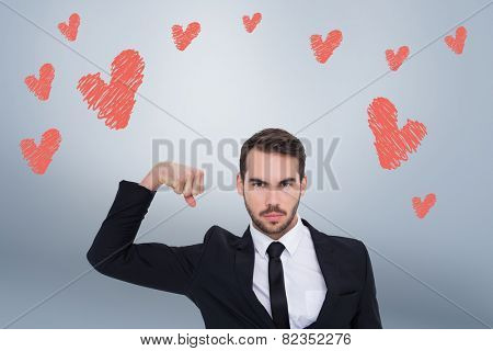 Businessman tensing arm muscle and looking at camera against grey vignette