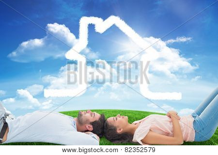 Attractive young couple lying down against green hill under blue sky