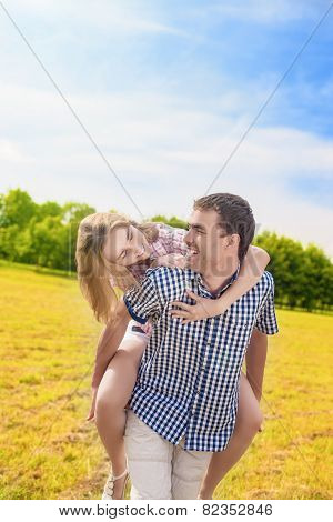 Happy Caucasian Couple Playing Outdoors In Summer. Having Fun While Piggybacking And Happiness Lifes
