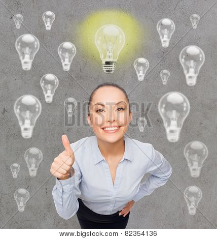 education, business, inspiration, gesture and people concept - smiling young woman in eyeglasses having idea and showing thumbs up over gray background with light bulbs