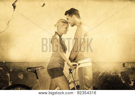 Cute couple together with their bicycles against grey background