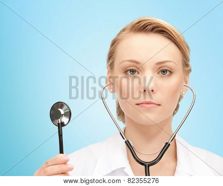 people, medicine, equipment and profession concept - young female doctor with stethoscope over blue background
