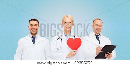 medicine, profession, teamwork and healthcare concept - group of smiling medics or doctors holding red paper heart shape, clipboard and stethoscopes over blue background