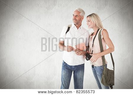 Happy tourist couple using the guidebook against white background
