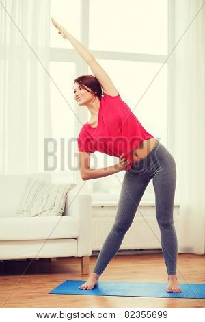 fitness, home and diet concept - smiling teenage girl streching at home