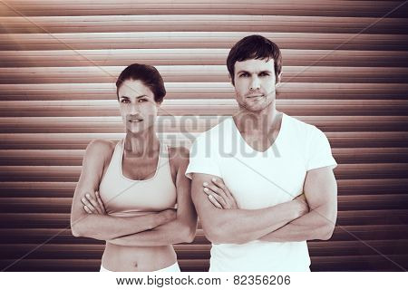 Portrait of a fit young couple with arms crossed against grey shutters