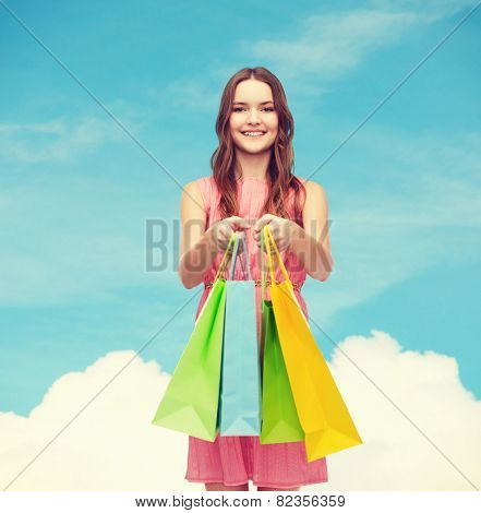 retail and sale concept - smiling woman in dress with many shopping bags