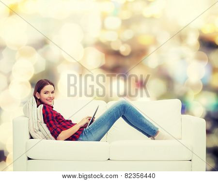 technology and happy people concept - teenage girl sitting on sofa with tablet pc