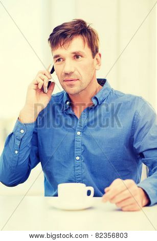 business, communication, modern technology concept - buisnessman with cell phone and cup of coffee