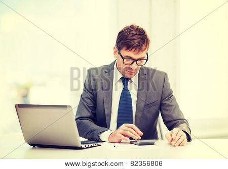 business, office, school and education concept - businessman with laptop computer, papers and calculator