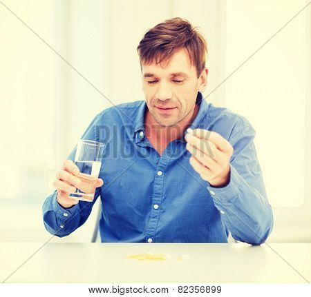 health, healthcare, medicine, medication, drugs, concept - ill man taking his pills at home