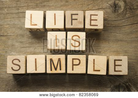 Life is Simple text on a wooden background