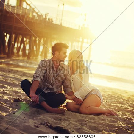 romantic couple sitting on beach with golden sunset by beach