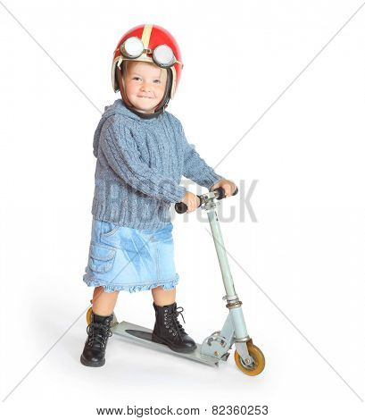 Little girl in retro motorcycle helmet driving her scooter. Road safety and insurance concept.