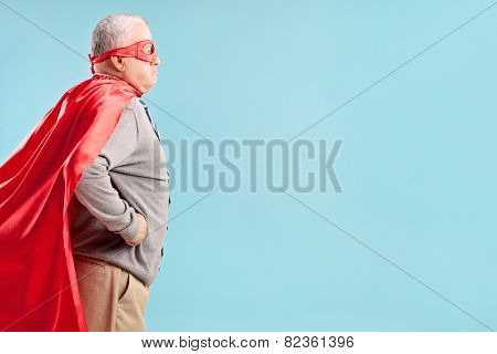 Studio shot of a senior in a superhero outfit on blue background