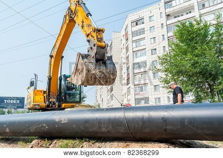 Using of excavator as crane for raising of tube