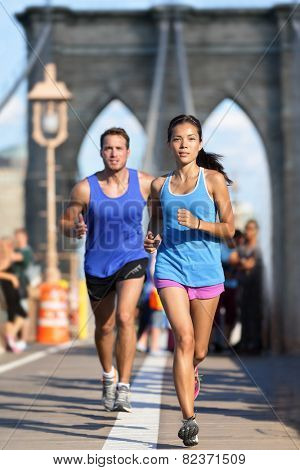 New York runners running training on Brooklyn bridge NYC during busy rush hours with tourists. Fit young couple doing their workout routine on a summer day.