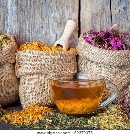 Healing Herbs In Hessian Bags And Healthy Tea Cup On Rustic Wooden Background, Herbal Medicine.