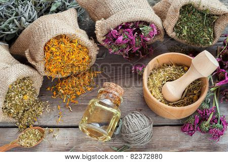 Healing Herbs In Hessian Bags, Wooden Mortar With Chamomile And Essential Oil On Rustic Table, Herba