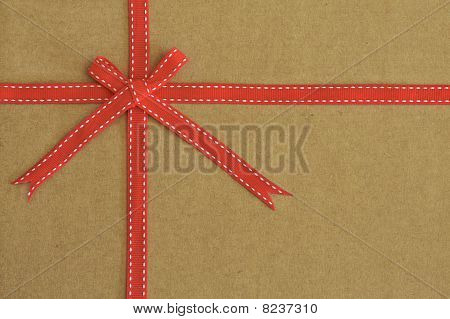 Red Ribbon Bow On Recycled Card As Background
