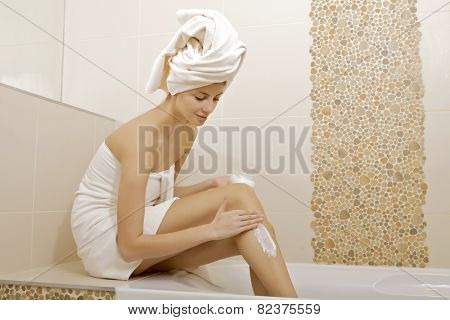 Attractive sexy and sensuality young adult beautiful brunette woman with white towel applying moisturizer cream on the long legs in home bathroom