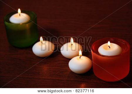 Glass Candlesticks And Candles On Wooden Table. Selective Focus On The Nearest Candle