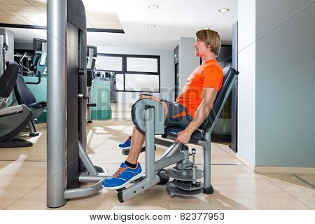 Hip abduction blond man exercise at gym indoor opening legs workout