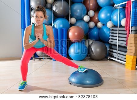 bosu one leg squat girl exercise at gym workout and swiss ball background