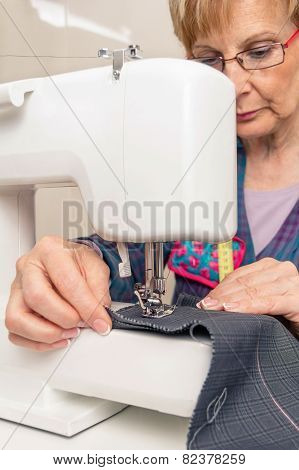 Senior seamstress woman working on sewing machine