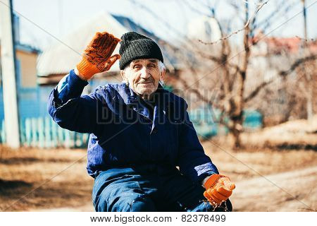 Cheerful Old Man In Workwear Sitting Outdoors