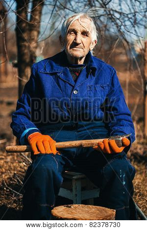Grandfather In Workwear Sitting Outdoors With Axe