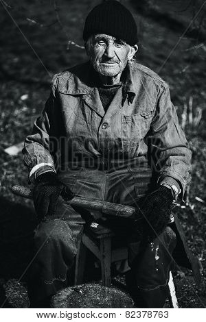 Monochrome Old Man In Workwear Sitting Outdoors With Axe