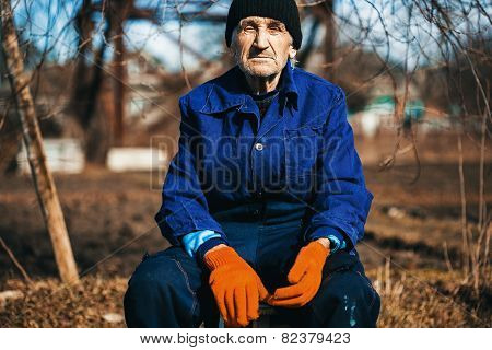 Old Man In Blue Workwear Sitting Outdoors
