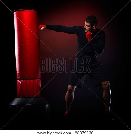 young man standing exercising with boxing bag in studio