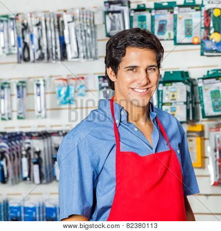 Portrait of handsome young worker in red apron smiling at hardware shop