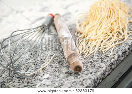 Boiled spaghetti pasta with rolling pin and wire whisk on countertop in commercial kitchen