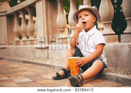 Boy In Hat Sitting Near Balustrade