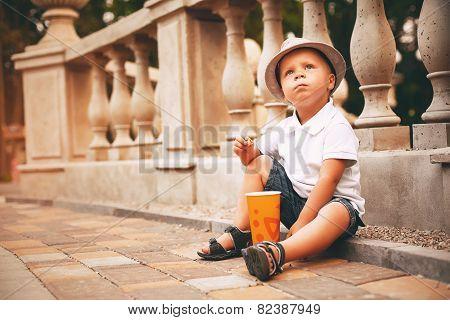 Boy In Hat Sitting On Sett
