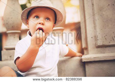 Cute Boy In Hat Near Balustrade