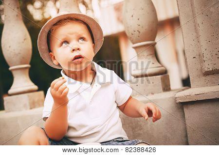 Cute Little Boy In Hat Near Balustrade