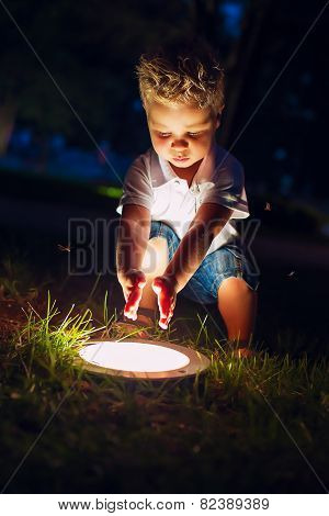 Little Blond Boy And Shiny Lamp At Night