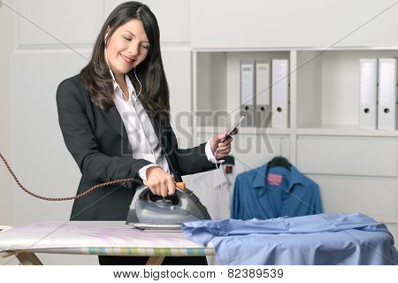 Happy Housewife Listening To Music While Ironing